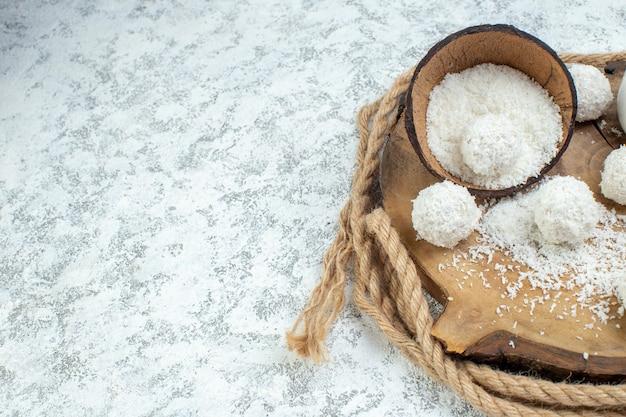 Mezza vista inferiore ciotola di polvere di cocco palline di cocco su tavola di legno su sfondo grigio