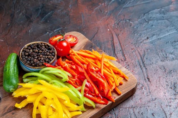 Vista a metà inferiore peperoni tagliati colorati pepe nero pomodori cetriolo sul tagliere sul tavolo rosso scuro