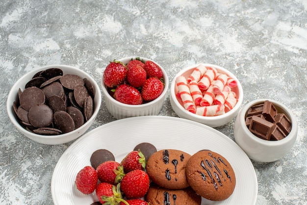 Bottom half view cookies strawberries and round chocolates on the white oval plate surrounded bowls with candies strawberries and chocolates on the background