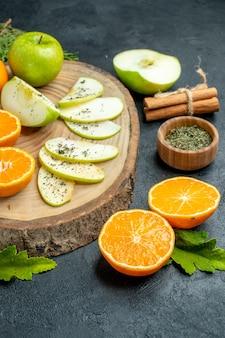下半分のビュー新鮮なリンゴとオレンジのスライスを木の板に乾燥ミントパウダーをボウルに入れシナモンスティック松の木の枝を黒いテーブルに