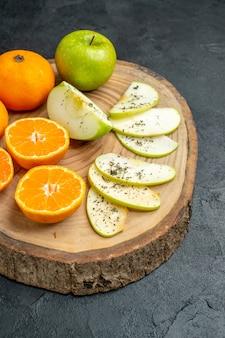 下半分は、黒いテーブルの上の木の板に乾燥ミントパウダーと新鮮なカットリンゴとオレンジを表示します