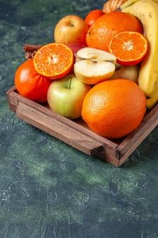 Нижняя половина вида свежие фрукты и палочки корицы на деревянном подносе на темном фоне свободного места