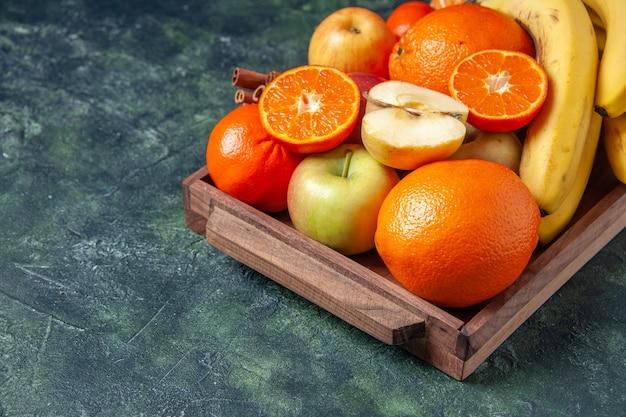 Mezza vista inferiore frutta fresca e bastoncini di cannella su vassoio di legno su sfondo scuro spazio copia