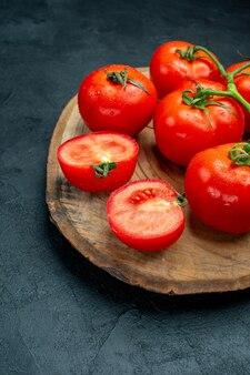下半分は暗いテーブルの上の新鮮な赤いトマトの木の板を表示します