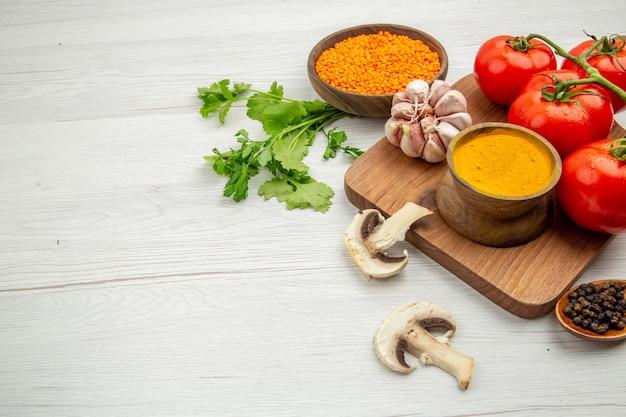 Mezza vista inferiore ramo di pomodoro fresco aglio curcuma ciotola sul tagliere funghi ciotola di lenticchie sul tavolo grigio spazio libero