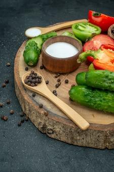 Mezza vista inferiore verdure fresche cetrioli pepe nero e sale in cucchiai di legno e ciotole pomodori rossi e verdi peperone su tavola di legno sul tavolo scuro