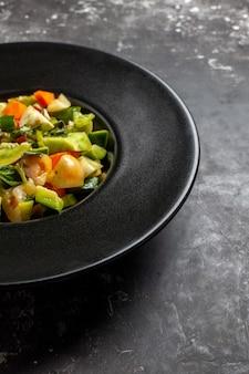 어두운 배경에 타원형 접시에 아래쪽 절반 보기 녹색 토마토 샐러드