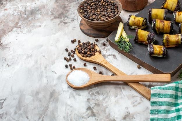 Involtini di melanzane grigliate vista a metà inferiore su tagliere di legno spezie in cucchiai di legno su sfondo nudo spazio libero free