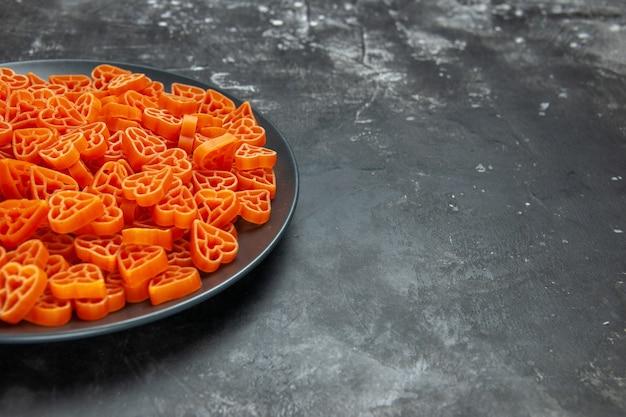 Bottom half view heart shaped italian pasta on black oval plate on dark surface