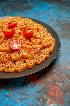 Bottom half view italian pasta hearts cut cherry tomatoes on black oval plate on blue surface