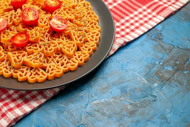 아래쪽 절반보기 이탈리아 파스타 마음 빨간색 흰색 체크 무늬 테이블에 타원형 접시에 체리 토마토를 잘라