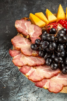 Bottom half view meat slices cheese grapes and pomegranate on oval serving board on dark