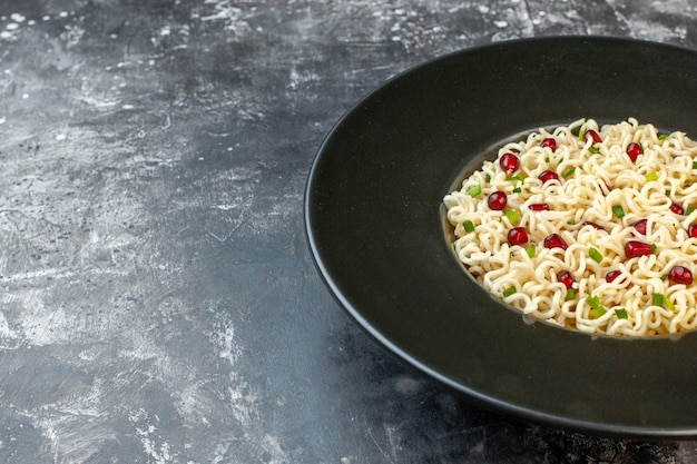 Bottom half view ramen noodle flavored by pomegranate on dark table free space