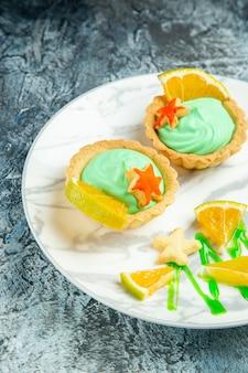 어두운 표면에 접시에 녹색 과자 크림과 레몬 슬라이스가있는 아래쪽 절반보기 작은 타르트