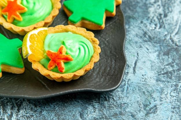회색 표면에 검은 접시에 녹색 과자 크림 크리스마스 트리 비스킷과 하단 절반보기 작은 타르트