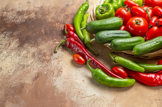 Bottom half view vegetables in a wicker basket surrounded by peppers and cherry tomatoes on amber background