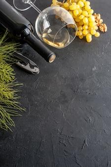 아래쪽 절반 보기 와인 잔 신선한 노란색 포도 호두 와인 병 xmas 빨간 열매는 복사 장소가 있는 검은색 테이블에 있습니다.