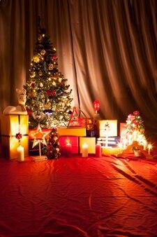 花輪と装飾が施されたクリスマスツリーの底。木の一番下にはたくさんのギフトボックスと燃えるろうそくがあります。装飾的でお祝いの緑の木