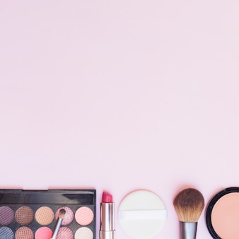 Bottom row of cosmetics product on pink background