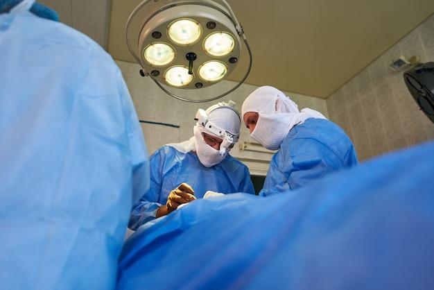 Вид снизу вверх лиц хирургов под круглой хирургической лампой Premium Фотографии