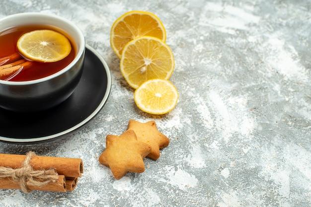 Вид снизу чашка чая, ломтики лимона, палочки корицы на серой поверхности, место для копирования