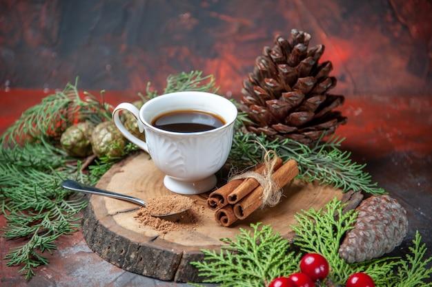 Вид снизу чашка чая на деревянной доске палочки корицы сосновая шишка ветки сосны на темном фоне
