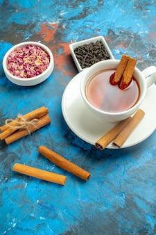 Вид снизу чашка чая с палочками корицы на сине-красной поверхности