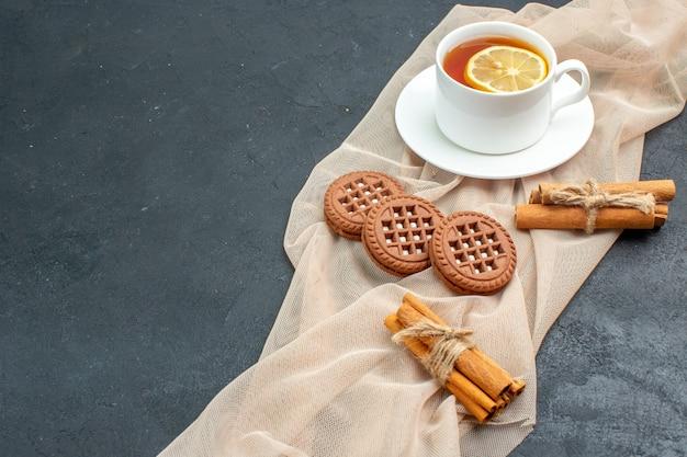 Вид снизу чашка чая с лимоном, палочками корицы, печеньем на бежевой шали на темной поверхности, свободное пространство