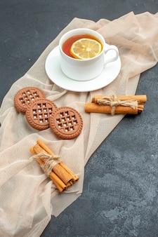 Вид снизу чашка чая с печеньем в палочках с лимоном и корицей на бежевой шали на темной поверхности