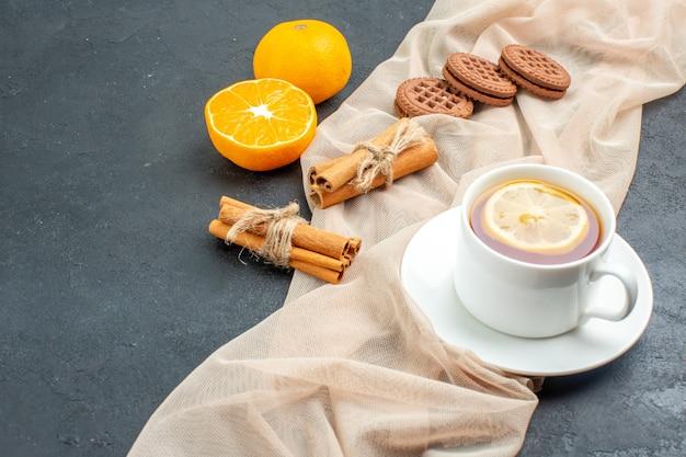 Вид снизу чашка чая с лимоном, печеньем в палочках корицы на бежевой шали оранжевого цвета на темной поверхности