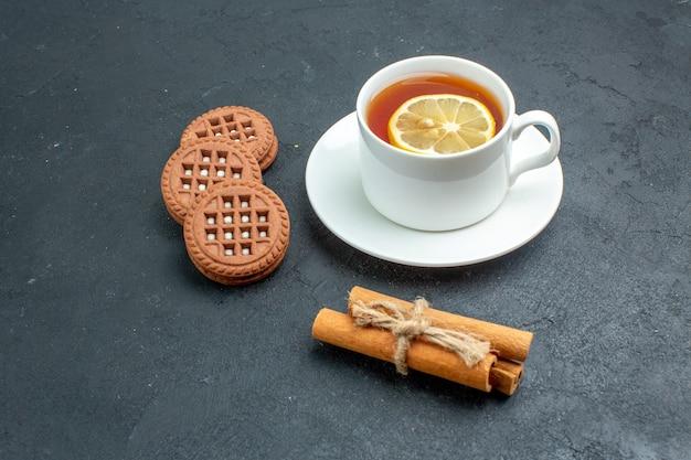 Вид снизу чашка чая с печеньем в палочках с лимоном и корицей на темной поверхности