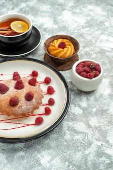 底面図灰色の表面の楕円形のプレートにレモンスライスとシナモンスティックベリーケーキとお茶のカップ