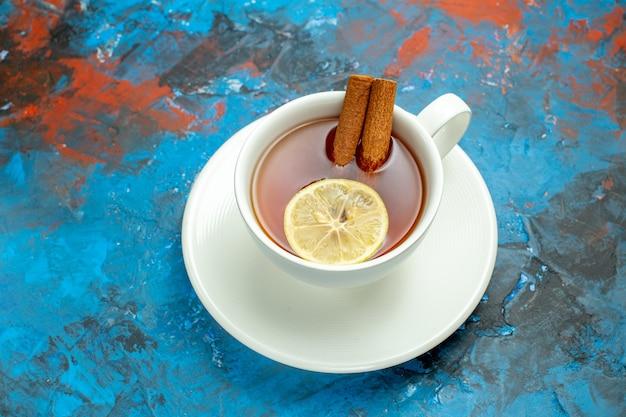 Вид снизу чашка чая с ломтиком лимона и палочками корицы на сине-красной поверхности