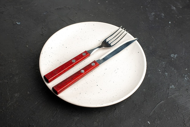 底面図黒い表面の白いサラダプレートにフォークとナイフ 無料写真