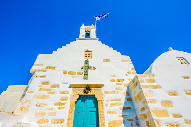 Bottom view of anchient white greek church with bright blue door on the greek street