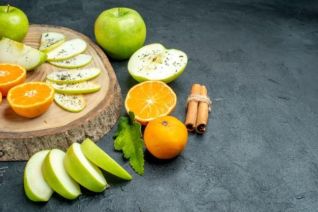 검은색 테이블 복사 장소에 밧줄로 묶인 나무 판자에 있는 아래쪽 보기 사과와 만다린 조각