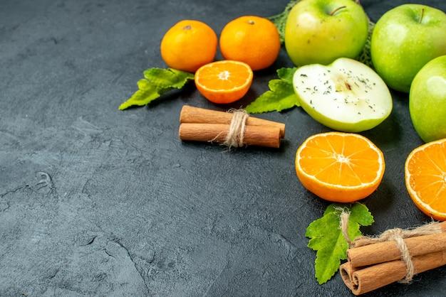 Vista dal basso fette di mela e arancia bastoncini di cannella legati con una corda sul posto della copia del tavolo nero