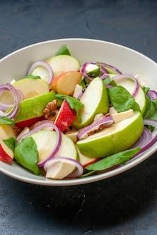 Вид снизу яблочный салат в миске на темном изолированном столе