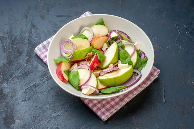 暗いテーブルの上のボウルピンクホワイト市松模様のナプキンの底面図アップルサラダ