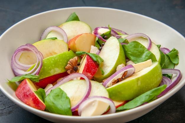 Вид снизу яблочный салат с луком и другими начинками на глубокой тарелке на темном столовом корме фото