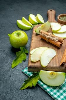 底面図まな板の上のリンゴのスライスとシナモンボウルの乾燥したミントパウダー暗いテーブルの上のリンゴの緑のテーブルクロス