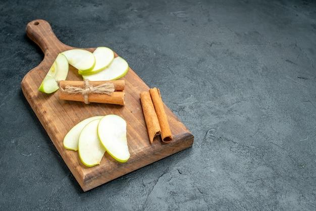 Fette di mela vista dal basso e bastoncini di cannella sul tagliere sul tavolo scuro con spazio libero