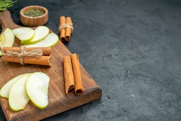 Vista dal basso fette di mela e bastoncini di cannella sul tagliere coltello e forchetta polvere di menta essiccata in una ciotola sul tavolo scuro con spazio libero