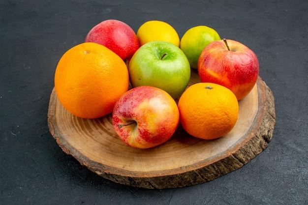 Вид снизу яблоки лимон апельсины на деревянной доске на темной поверхности