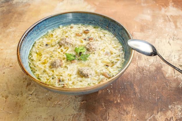 Vista dal basso erishte azero in una ciotola un cucchiaio su fondo beige Foto Gratuite