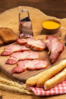 Vista dal basso fette di becon sul tagliere grattugia per pane spiga di grano su tavola di legno