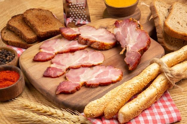 Вид снизу ломтики бекона на разделочной доске красный и черный перец в небольших мисках коричневый и белый хлеб на деревянном столе