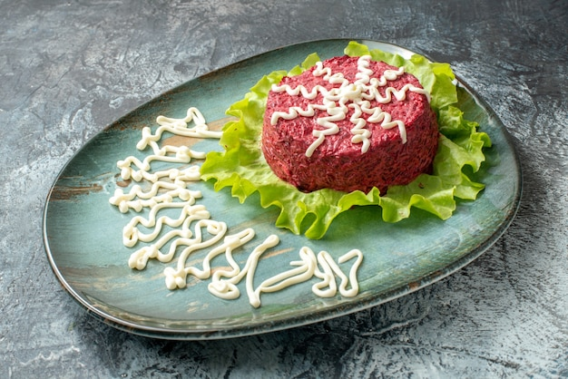 Bottom view beet salad decorated with mayonnasie and lettuce on plate on grey table