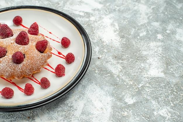 복사 공간 회색 표면에 흰색 타원형 접시에 하단보기 베리 케이크
