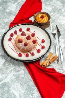 Вид снизу ягодный торт на белой овальной тарелке красная шаль, вилка для печенья и обеденный нож, палочки корицы на серой поверхности